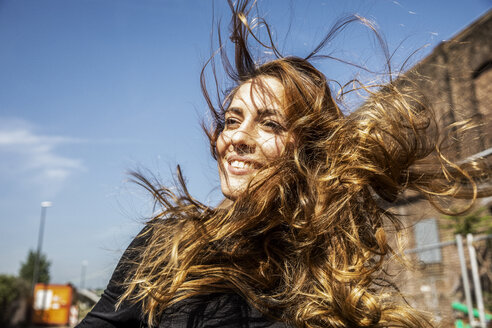 Portrait of smiling woman with blowing hair - FMKF05090
