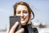 Portrait of smiling woman taking selfie with smartphone - FMKF05093