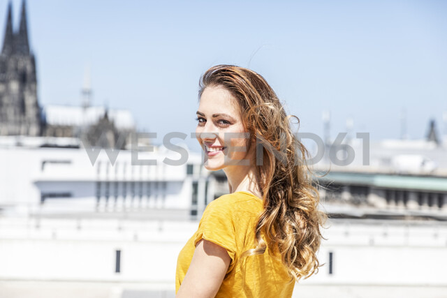 Germany, Cologne, portrait of smiling woman on roof terrace - FMKF05105 - Jo Kirchherr/Westend61