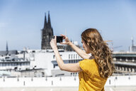 Germany, Cologne, woman taking photo with smartphone on roof terrace - FMKF05108