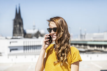 Germany, Cologne, portrait of smiling woman on the phone - FMKF05117