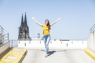 Germany, Cologne, happy woman on ramp of parking level with Cologne Cathedral in the background - FMKF05120