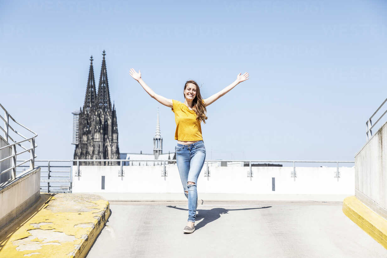 Germany, Cologne, happy woman on ramp of parking level with Cologne Cathedral in the background - FMKF05120 - Jo Kirchherr/Westend61