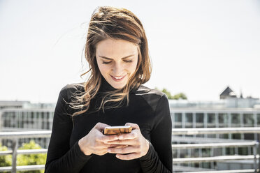 Smiling woman text messaging on roof terrace - FMKF05123