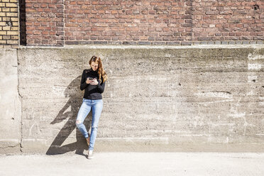 Woman with leaning against wall using cell phone - FMKF05126