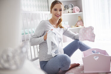 Pregnant woman with baby clothes in baby room - ABIF00528