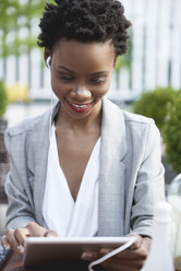 Portrait of smiling businesswoman using digital tablet and earphones outdoors - ABIF00537