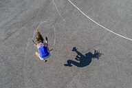 Aerial view of young woman skipping rope, shadow - STSF01598