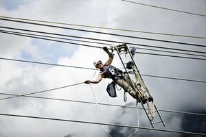 Fitter with ladder, pulling along high-voltage power line - CVF00695