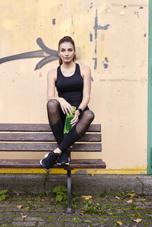 Sportive woman with water bottle sitting on bench - MMIF00116