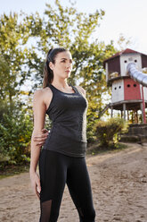 Sportive woman stretching arm in park - MMIF00119