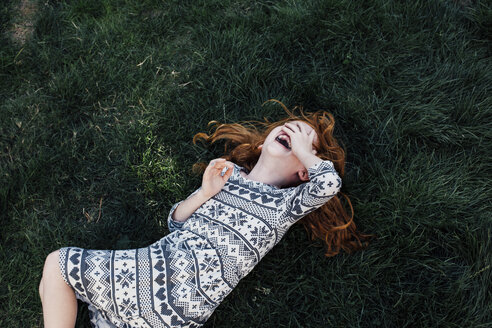 High angle view of girl lying on grass covering face laughing - ISF09175