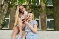 Two young women sharing cell phone and earphones outdoors - MMIF00134