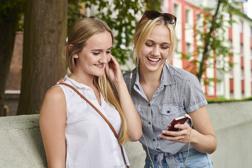 Two happy young women sharing cell phone and earphones outdoors - MMIF00137
