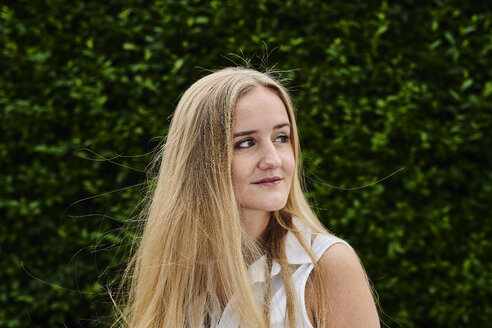 Blond young woman at a hedge looking sideways - MMIF00140
