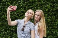 Two young women posing for a selfie at a hedge - MMIF00143