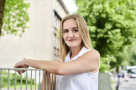 Portrait of smiling blond young woman at a fence - MMIF00149