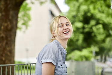 Laughing blond young woman at a fence - MMIF00152