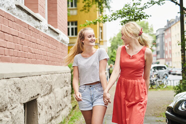 Two happy young women walking hand in hand in the city - MMIF00161