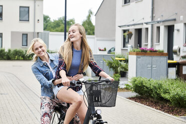 Two happy young women riding bicycle together on one bike - MMIF00170