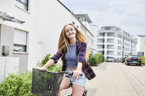 Happy young woman riding bicycle in housing area - MMIF00173