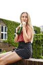 Young woman sitting on brick wall drinking a smoothie - MMIF00176