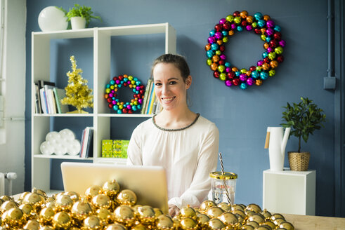Portrait of smiling woman sitting at table with laptop and many golden Christmas baubles - MOEF01332