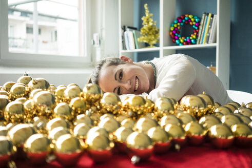 Smiling woman sitting at table with many golden Christmas baubles - MOEF01335