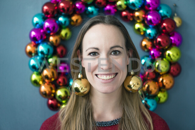 Portrait of smiling woman wearing golden Christmas bauble earrings - MOEF01338 - Robijn Page/Westend61