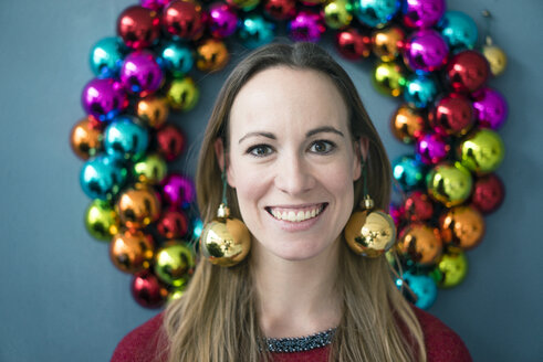 Portrait of smiling woman wearing golden Christmas bauble earrings - MOEF01338