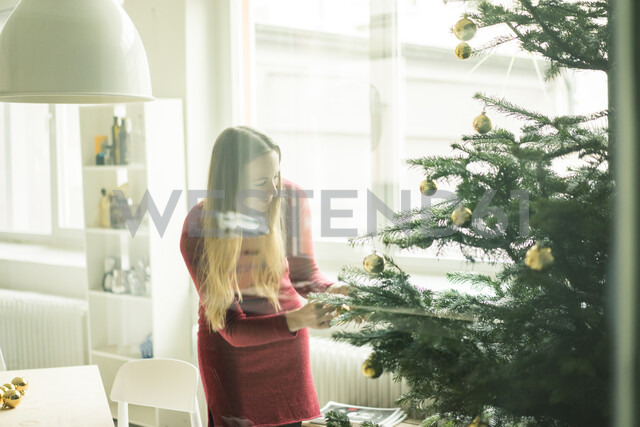 Smiling woman decorating Christmas tree - MOEF01344 - Robijn Page/Westend61