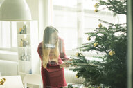 Smiling woman decorating Christmas tree - MOEF01344