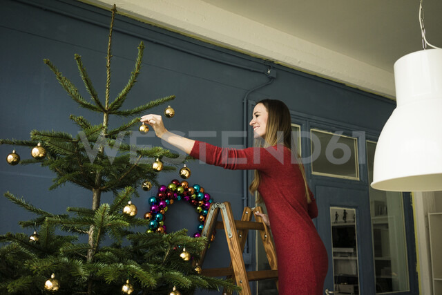 Smiling woman standing on ladder decorating Christmas tree - MOEF01347 - Robijn Page/Westend61