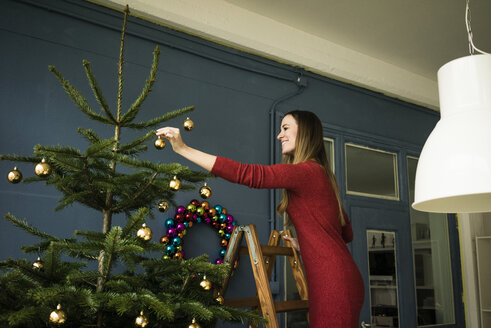 Smiling woman standing on ladder decorating Christmas tree - MOEF01347