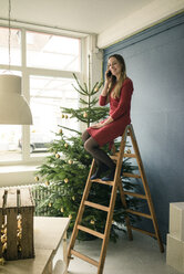 Woman on the phone sitting on ladder in a loft in front of Christmas tree - MOEF01350