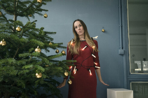 Portrait of woman with chain of lights standing besides Christmas tree - MOEF01353