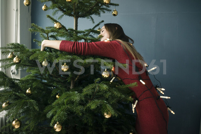 Woman hugging Christmas tree - MOEF01356