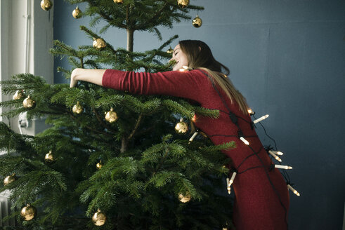 Woman hugging Christmas tree - MOEF01356