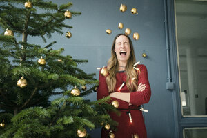 Screaming woman standing besides Christmas tree - MOEF01359