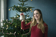 Portrait of smiling woman with   Christmas bell - MOEF01362