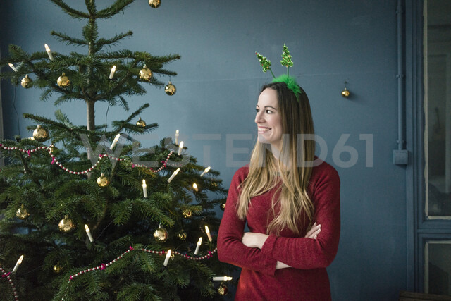 Content woman with Christmas headdress standing besides decorated Christmas tree - MOEF01365 - Robijn Page/Westend61