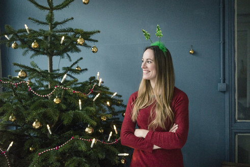 Content woman with Christmas headdress standing besides decorated Christmas tree - MOEF01365
