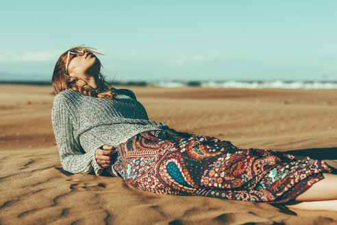 Young woman lying in desert landscape - OCAF00262