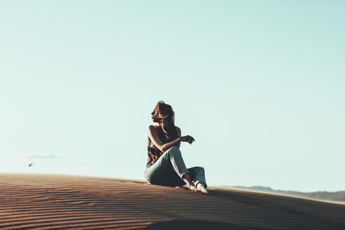 Young woman sitting in desert landscape - OCAF00271