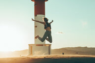 Young woman jumping in desert landscape at lighthouse - OCAF00274