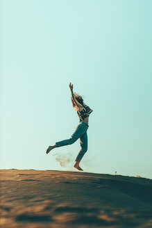 Young woman jumping in desert landscape - OCAF00277