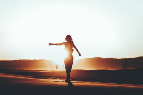 Silhouette of woman standing in desert landscape at sunset - OCAF00280
