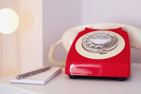 Close-up of red telephone with diary and pen on table at home - FSIF03149