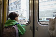 Rear view of boy looking through closed door while traveling in train - FSIF03152
