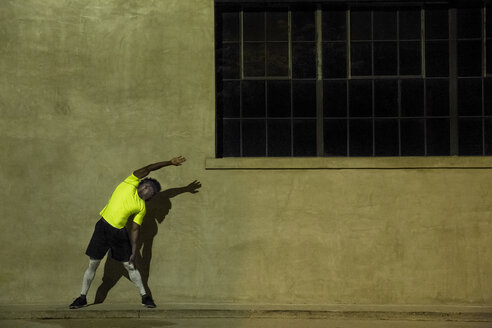 Young man exercising at night, in urban setting - ISF09224